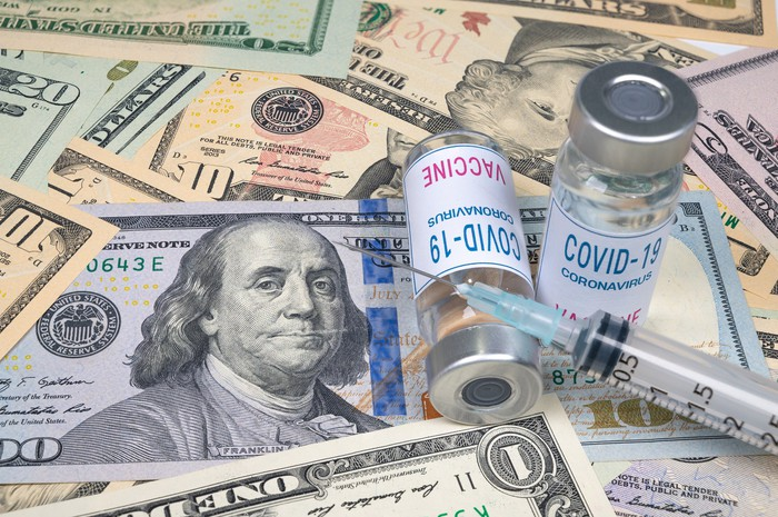 Two COVID-19 vaccine bottles and a syringe on top of U.S. cash