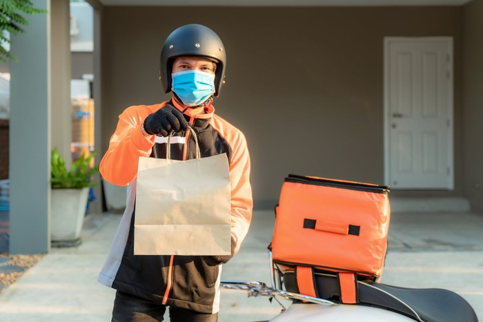 Masked food delivery driver holding a bag of food.