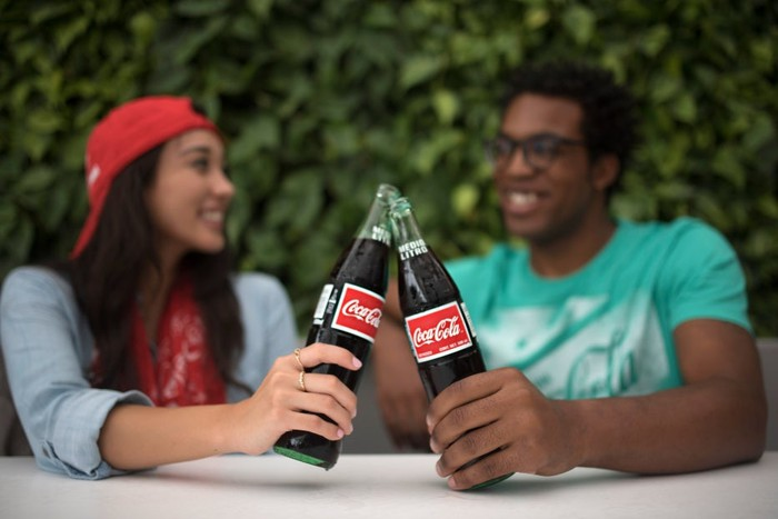 Two friends clanking their Coca-Cola bottles together while seated outside and talking.