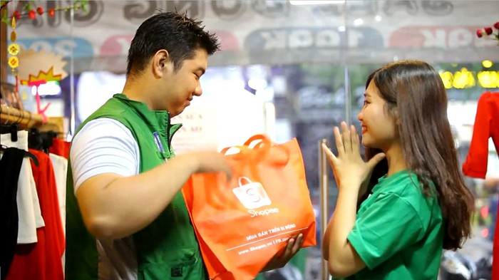 A man holding a Shopee bag, with his happy woman next to him.
