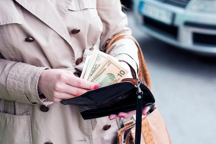 Close-up of a woman putting $10 bills into her wallet.