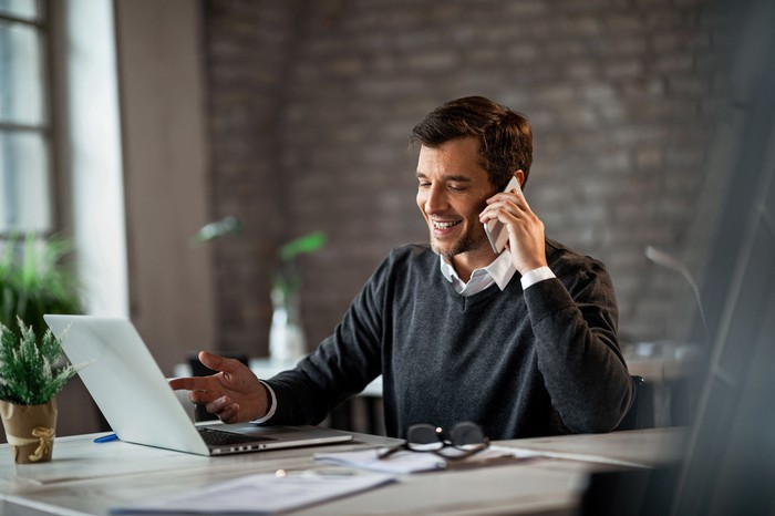 Man on phone in front of laptop