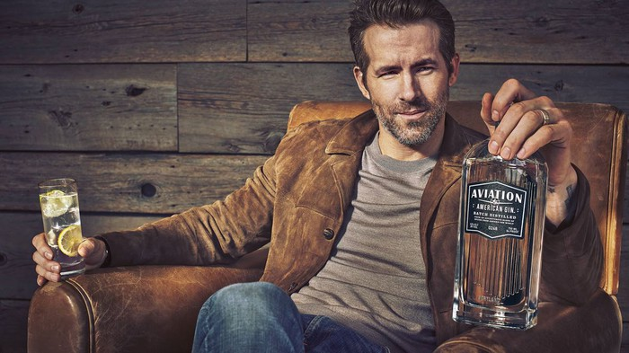 ryan reynolds in chair promoting aviation american gin bottle in his hand