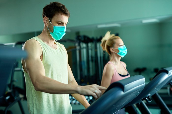 Two people in a gym working out while wearing masks.