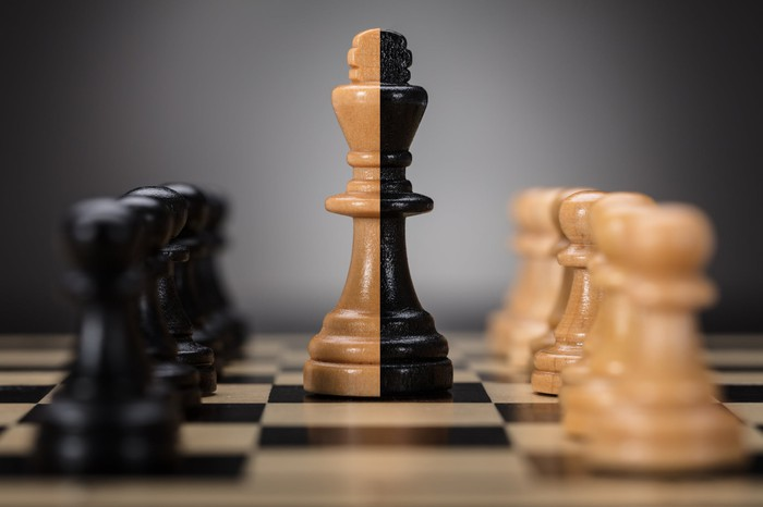 Chess pawn pieces are facing each other with a king piece in the center.
