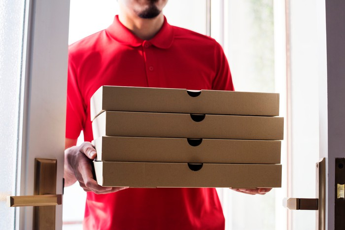 A young man delivering a stack of boxed pizzas.