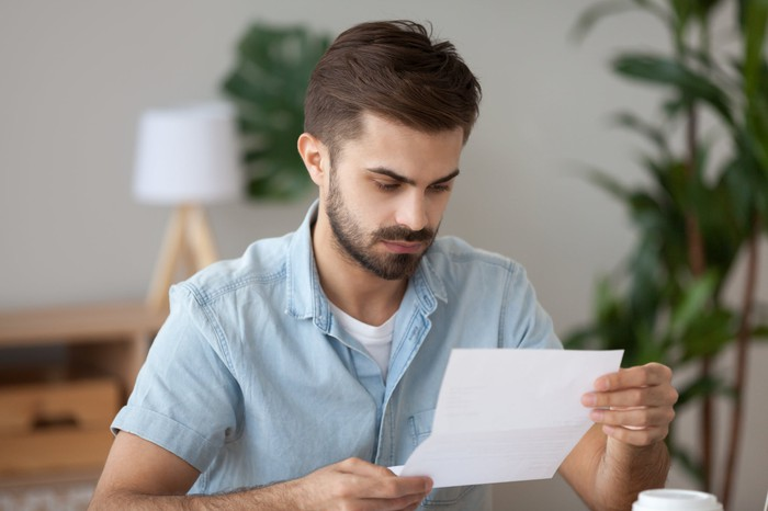 Man with serious expression reading document