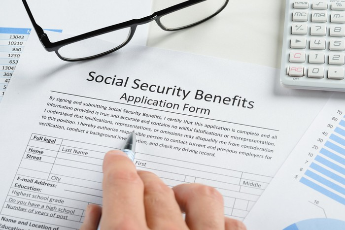 Hand holding pen and filling out a Social Security form, with glasses and a calculator on top of the papers.