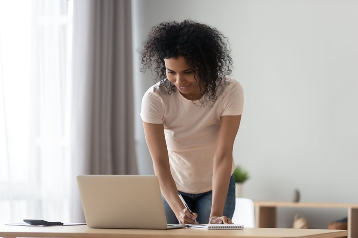 A woman stands, with notepad and pen, behind a laptop on a desk.