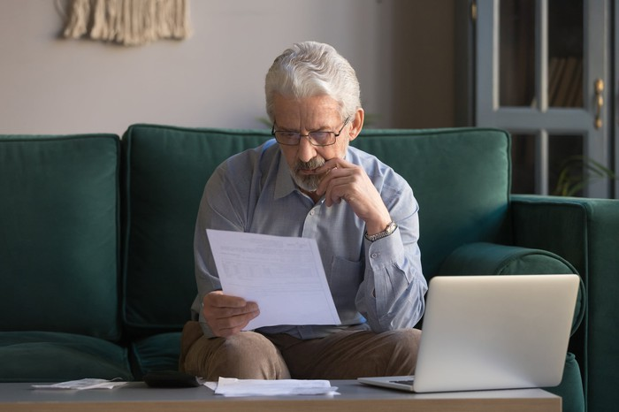 Older man with serious expression sitting on couch reading document in front of laptop