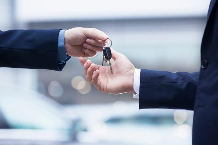 Closeup of one hand handing car keys to another.