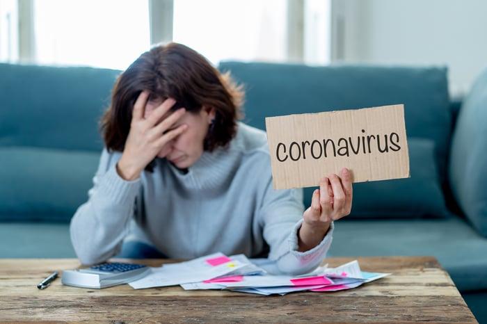 Woman overwhelmed with bills holding coronavirus sign.