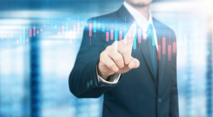 A man in a suit holds his finger up to a digital stock chart
