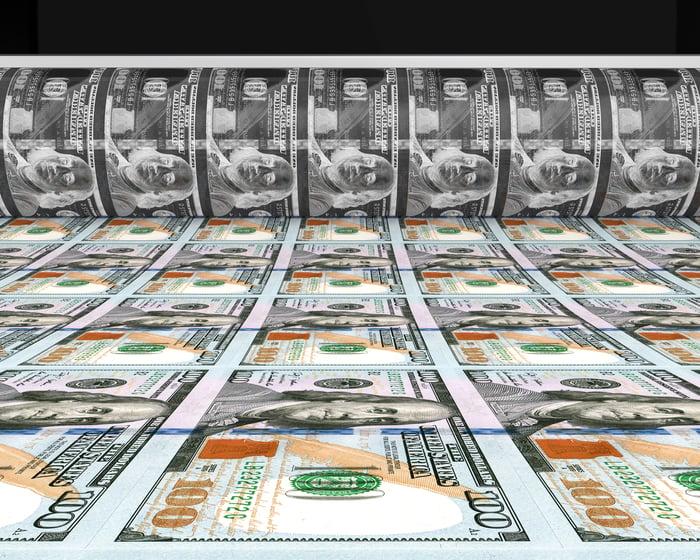 A sheet of $100 bills rolling off a printing press.