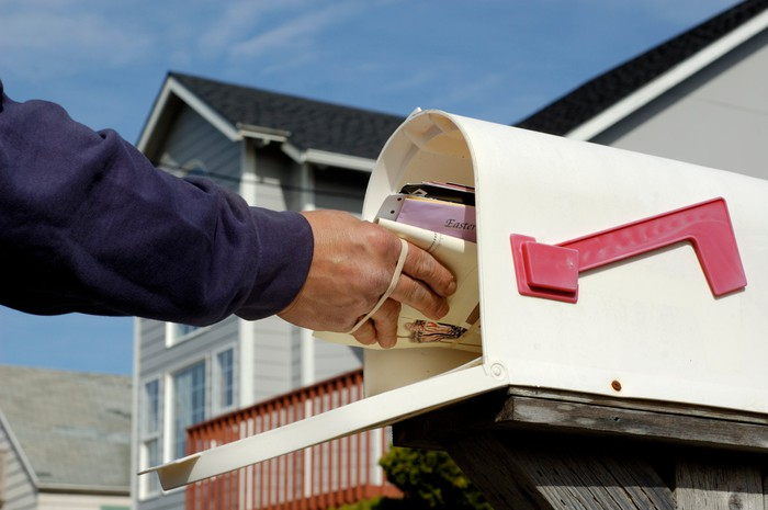 Mail being delivered to a mailbox.