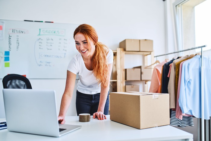 Online business owner looking at laptop while preparing deliveries for clients.