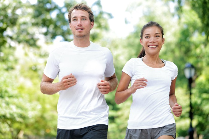 Man and woman jogging side by side in white tops
