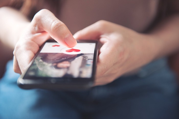A person using a smartphone on which there is a picture of a person and red cartoon hearts