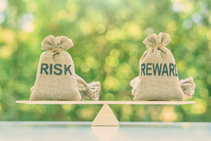 On a tabletop outdoors, a bag labeled risk is balanced on a fulcrum across from a bag labeled reward.