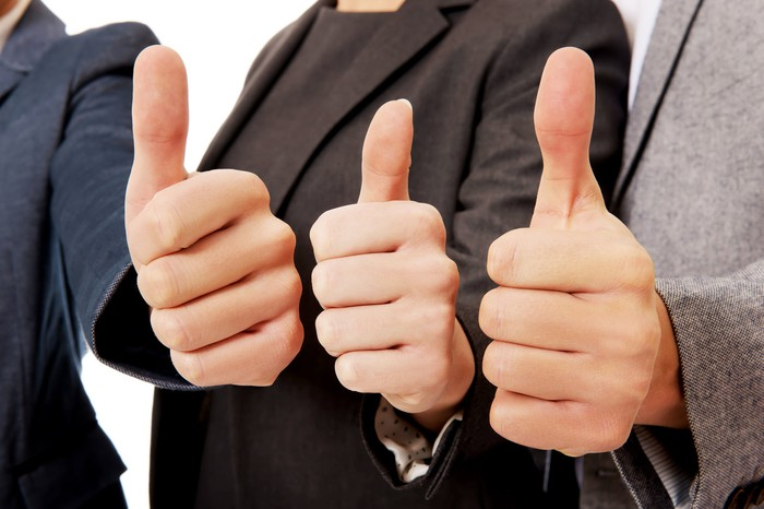 Three people in suits with their thumbs up.