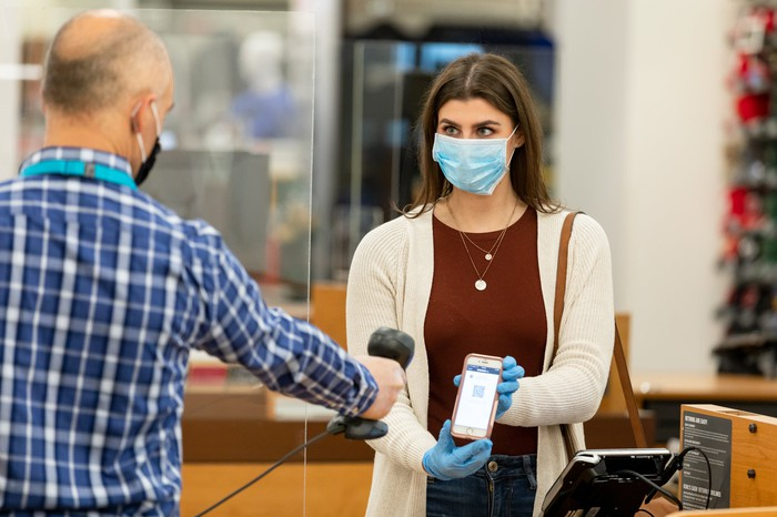A Kohl's employee wearing a face mask scans a customer's phone for safe checkout.