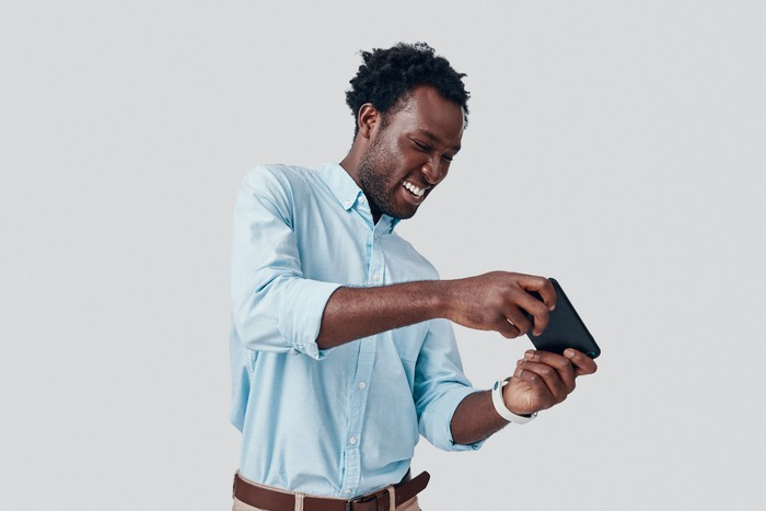 Man playing mobile game on smartphone
