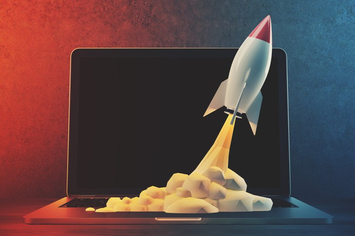 A computer rendering of a rocket taking off from a laptop keyboard.