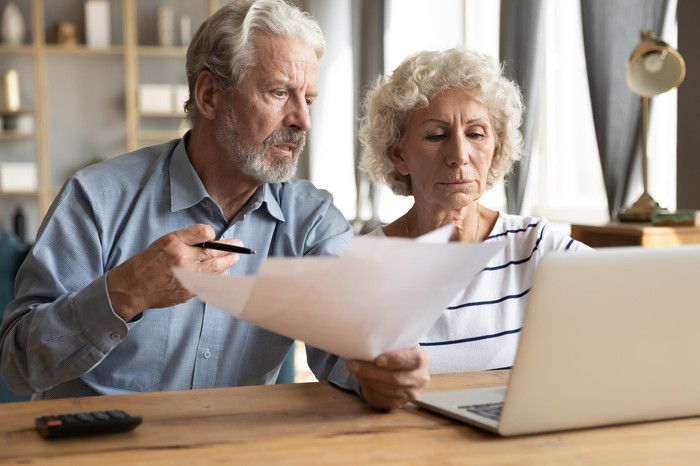Older man holding documents sitting next to older woman at laptop