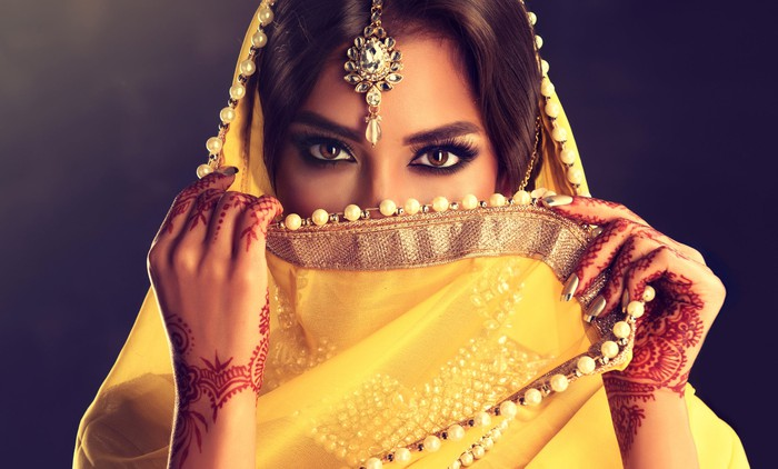 An Indian woman with henna on her hands and a yellow scarf partially covering her face.