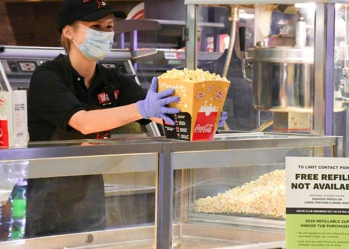 Cinemark worker with mask and gloves serves popcorn