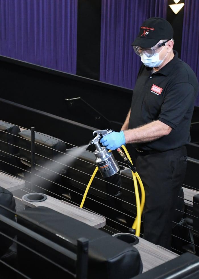 Cinemark worker sprays sanitizer on movie seats