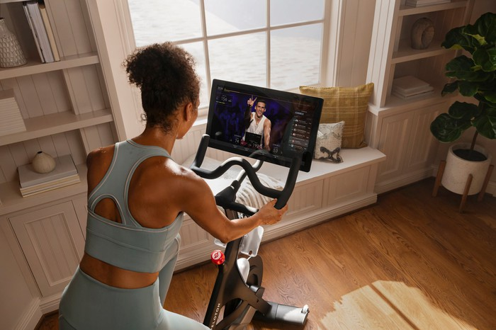 A woman is exercising on a Peloton bike while watching a digital fitness class.