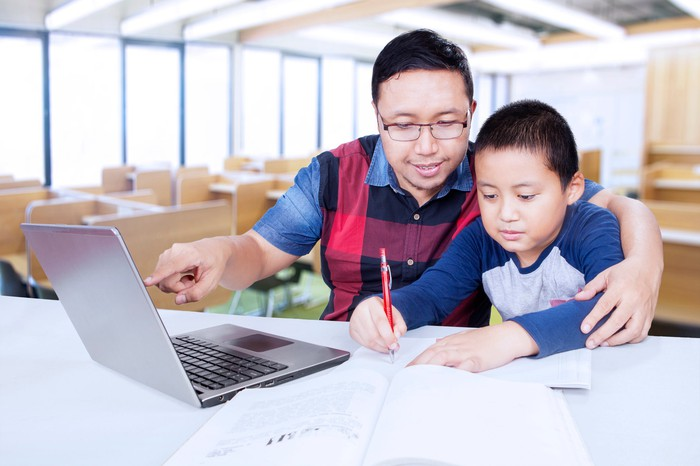 A man watching a little boy write and pointing to a laptop screen