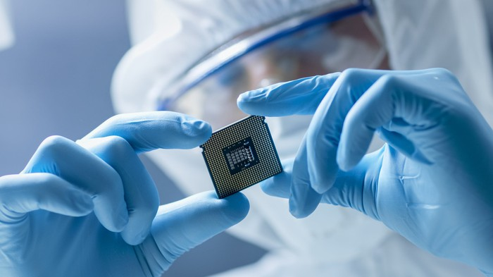 A worker in a lab suit, gloves, and a mask holding a semiconductor chip