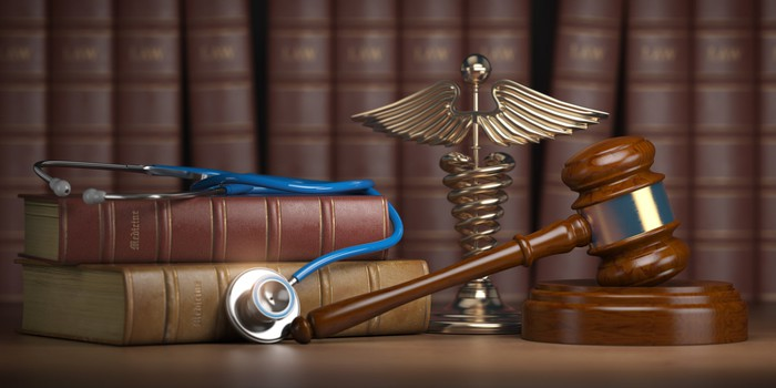 Stethescope and gavel on desk with caduceus ornament and books.