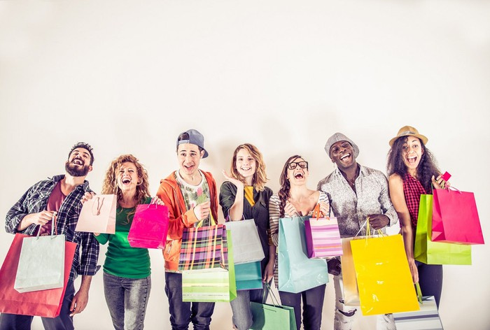 Seven people carrying shopping bags of various colors.