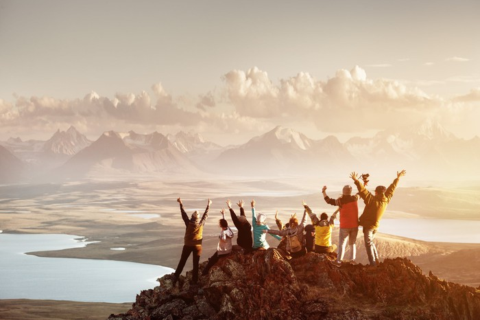 A group of people celebrating on a mountain peak.