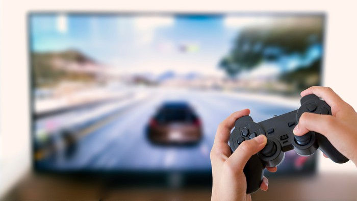 A hand holding a video game controller with a game displayed on a TV in the background.