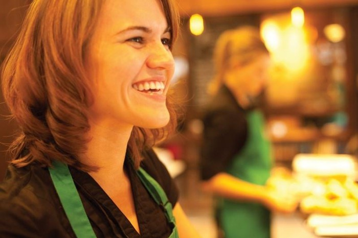 A smiling Starbucks employee working behind the counter.