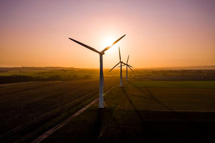 Three wind turbines at sunrise.