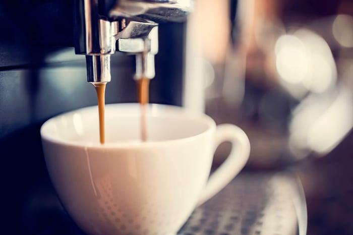 Coffee machine dispensing coffee into a coffee cup