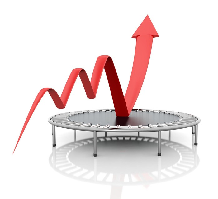 A stock chart arrow bouncing higher on a trampoline.