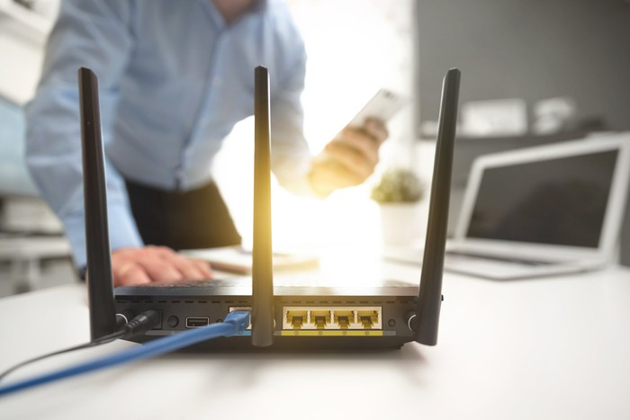 a wireless router in the foreground a man using a smart phone in the background