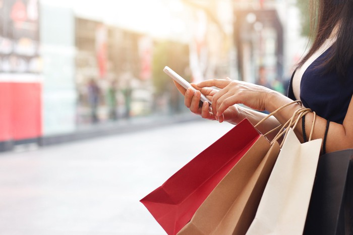 A woman checks her smartphone while holding shopping bags.