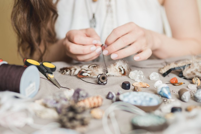 Woman crafting necklace with shells