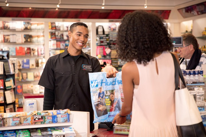 Sales clerk handing a shopping bag to a customer in a Hudson convenience store