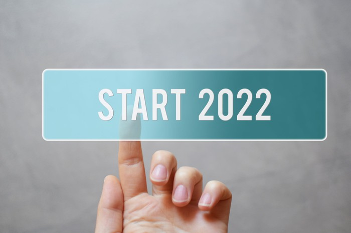 Hand touches a button that reads Start 2022