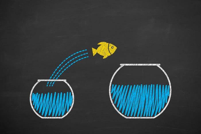 A fish jumping from a small fish bowl to a larger fish bowl.