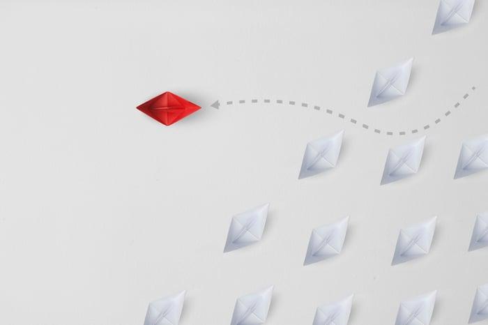 A red kite flying through a crowd of white kites.