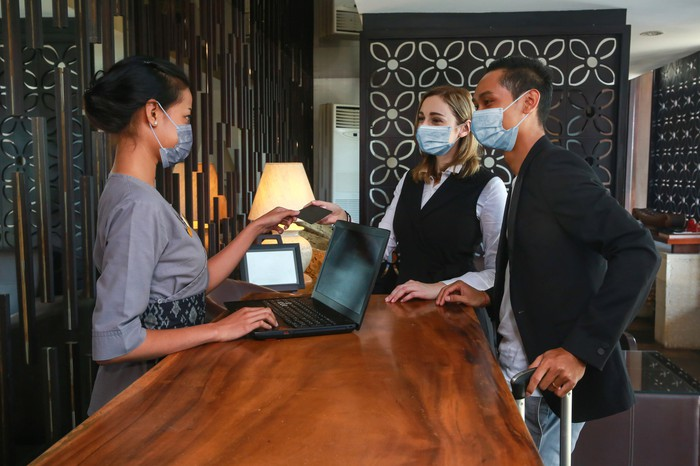 A couple checking into a hotel wearing masks.